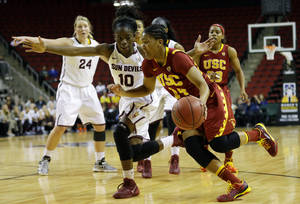Photo - Southern California's guard Ariya Crook, front right, drives around Arizona State's Promise Amukamara (10) in the second half of an NCAA college basketball game in the second round of the Pac-12 women's tournament on Friday, March 7, 2014, in Seattle. USC won 59-57. (AP Photo/Ted S. Warren)