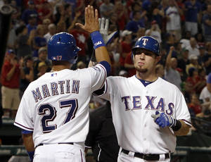 Photo - Texas Rangers' Leonys Martin (27) high-fives Josh Hamilton (32) after Hamilton's two-run home run in the seventh inning of a baseball game against the Detroit Tigers in Arlington, Texas, Monday, June 25, 2012. The Tigers won 8-2. (AP Photo/Richard Rodriguez) ORG XMIT: TXRR109