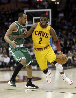Photo - Cleveland Cavaliers' Kyrie Irving (2) drives past Boston Celtics' Avery Bradley (0) during the second quarter of an NBA basketball game Tuesday, Jan. 22, 2013, in Cleveland. (AP Photo/Tony Dejak)