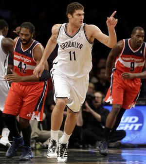 Photo - Brooklyn Nets' Brook Lopez points after scoring during the first half of an NBA basketball game against the Washington Wizards on Wednesday, Dec. 18, 2013, in New York. (AP Photo/Seth Wenig)
