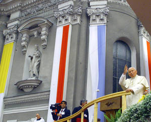 Photo - FILE - In this June 16, 1999 file photo Pope John Paul II waves from outside the basilica during his visit to Wadowice, Poland, the town where he was born and grew up. The basilica was his parish church, where he was baptized, served as an altar boy and stopped to pray on his way to school. A central point in Wadowice, the basilica has a chapel dedicated to John Paul with a reliquary containing a drop of his blood. (AP/Photo Rudi Blaha, File)