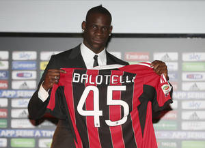 Photo - Italian striker Mario Balotelli poses with his new AC Milan jersey during an official presentation at the San Siro stadium in Milan, Italy, Friday, Feb. 1, 2013. Balotelli is expected to make his official debut for the Rossoneri against Udinese after his move from Manchester City. Balotelli finalised a €20 million transfer returning to Italy after a turbulent 2 1/2 years in the Premier League. (AP photo/Antonio Calanni) (AP Photo/Antonio Calanni)