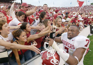 Photo - DALLAS, Saturday,10/11/2003: University of Oklahoma vs. University  of Texas college football at Cotton Bowl. Defensive back Brandon Everage celebrates with OU fans after Sooners defeated Texas, 65-13. Staff photo by Jim Beckel.