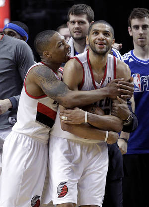 Photo - Portland Trail Blazers guard Damian Lillard, left, hugs teammate Nicolas Batum after winning an NBA basketball game against the Los Angeles Clippers in Portland, Ore., Saturday, Jan. 26, 2013.  Both players scored 20 points each as the Trail Blazers won 101-100. (AP Photo/Don Ryan)