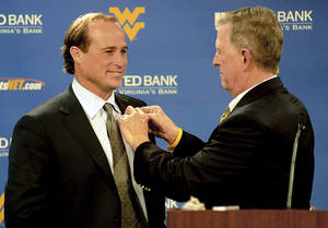 photo - New West Virginia University college football offensive coordinator and coach-in-waiting Dana Holgorsen, left, gets a WVU football team pin from coach Bill Stewart at the start of a news conference Wednesday, Dec. 22, 2010, in Morgantown, W.Va. After one season as offensive coordinator, Holgorsen will take over for Stewart in 2012. (AP Photo/The Dominion-Post, ) ORG XMIT: WVMOR101