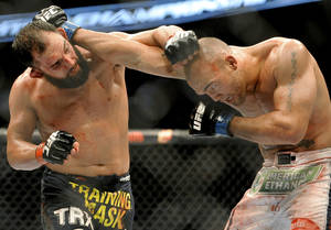 Photo - Johny Hendricks, left, and Robbie Lawler exchange punches during a UFC 171 mixed martial arts welterweight title bout, Saturday, March 15, 2014, in Dallas. Hendricks won by decision. (AP Photo/Matt Strasen)