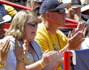 Photo - Mickey, left, and Joe Henderson cheer during Thursday's California-LSU game at ASA Hall of Fame Stadium. Their daughters, Jolene and Danielle, play for Cal.  Photo by Bryan Terry, The Oklahoman