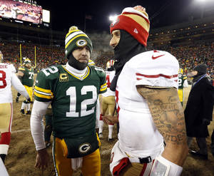 Photo - Green Bay Packers quarterback Aaron Rodgers (12) talks to San Francisco 49ers quarterback Colin Kaepernick (7) after an NFL wild-card playoff football game, Sunday, Jan. 5, 2014, in Green Bay, Wis. The 49ers won 23-20. (AP Photo/Mike Roemer)