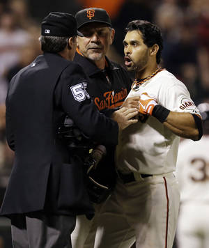Photo -   San Francisco Giants' Angel Pagan, right, is held back by manager Bruce Bochy, center, as he argues with home plate umpire Angel Hernandez after a strike out during the sixth inning of a baseball game against the Colorado Rockies on Tuesday, Sept. 18, 2012 in San Francisco. (AP Photo/Marcio Jose Sanchez)
