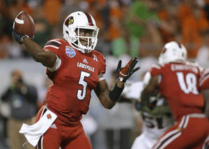 Photo - Louisville quarterback Teddy Bridgewater throws a pass against Miami during the first half of the Russell Athletic Bowl NCAA college football game in Orlando, Fla., Saturday, Dec. 28, 2013. (AP Photo/John Raoux)