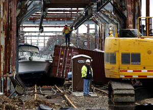 photo -   Workers try to clear boats and debris from the New Jersey Transit Morgan draw bridge Wednesday, Oct. 31, 2012, in South Amboy, N.J., after Monday's storm surge from Sandy pushed boats and cargo containers onto the train tracks. Travel in the Northeast creaked back into motion on Wednesday, a grinding, patchy recovery that made it clear that stranded travelers will struggle to get around for days to come. (AP Photo/Mel Evans)(AP Photo/Mel Evans)
