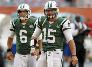 Photo -   FILE - In this Sept. 23, 2012, file photo, New York Jets quarterbacks Tim Tebow (15) and Mark Sanchez (6) warm up before an NFL football game against the Miami Dolphins in Miami . (AP Photo/Wilfredo Lee, File)