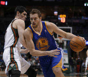Photo - Golden State Warriors' David Lee (10) drives to the basket against Milwaukee Bucks' Ersan Ilyasova, left, during the first half of an NBA basketball game Tuesday, Jan. 7, 2014, in Milwaukee. (AP Photo/Jeffrey Phelps)