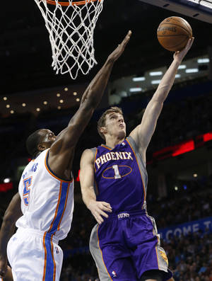 Photo - Phoenix Suns guard Goran Dragic (1) shoots in front of Oklahoma City Thunder center Kendrick Perkins (5) during the first quarter of an NBA basketball game in Oklahoma City, Friday, Feb. 8, 2013. (AP Photo/Sue Ogrocki)