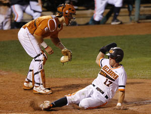 Photo - OSU's Gage Green slides home past Texas' Tres Barrera in the eight inning of a Big 12 Tournament baseball game between Oklahoma State University and the University of Texas at Chickasaw Bricktown Ballpark in Oklahoma City, Saturday, May 24, 2014. Photo by Bryan Terry The Oklahoman