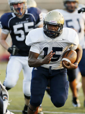 Photo - Southmoore's Karltrell Henderson carries the ball during an Aug. 17 scrimmage at Moore Stadium.  Photo by Nate Billings, The Oklahoman Archives