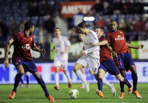 Photo - Real Madrid's Cristiano Ronaldo of Portugal, center, duels for the ball with Osasuna's Oier Sanjurjo, second right, during their Spanish Copa del Rey round-16 second leg soccer match at El Sadar stadium, in Pamplona, northern Spain, Wednesday, Jan. 15, 2014. (AP Photo/Alvaro Barrientos)