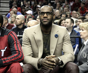Photo - Miami Heat forward LeBron James sits on the bench during the first half of the Heat's NBA basketball game against the Portland Trail Blazers in Portland, Ore., Saturday, Dec. 28, 2013. (AP Photo/Don Ryan)