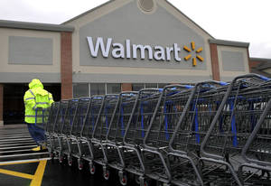 Photo - In this Tuesday, Nov. 13, 2012 photo a worker pulls a line of shopping carts toward a Walmart store in North Kingstown, R.I. Wal-Mart Stores Inc. reported a 9 percent increase in net income for the third quarter, but revenue for the world's largest retailer fell below Wall Street forecasts as its low-income shoppers continue to grapple with an uncertain economy. (AP Photo/Steven Senne) ORG XMIT: NYBZ163