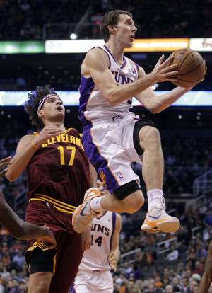 photo -   Phoenix Suns' Goran Dragic, right, of Slovenia, drives past Cleveland Cavaliers' Anderson Varejao, of Brazil, during the second half of an NBA basketball game on Friday, Nov. 9, 2012, in Phoenix. (AP Photo/Matt York)