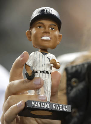 Photo - A fan displays a Mariano Rivera bobblehead doll during the New York Yankees' baseball game against the Tampa Bay Rays, Tuesday, Sept. 24, 2013, in  New York. (AP Photo/Kathy Willens)