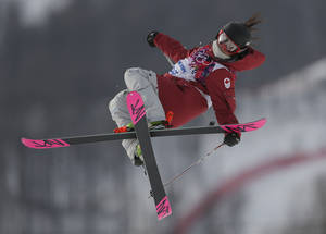 Photo - Canada's Yuki Tsubota takes a jump during the women's freestyle skiing slopestyle qualifying at the Rosa Khutor Extreme Park, at the 2014 Winter Olympics, Tuesday, Feb. 11, 2014, in Krasnaya Polyana, Russia.(AP Photo/Sergei Grits)