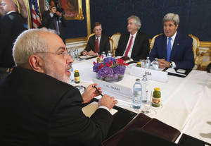 Photo - Iran's Foreign Minister Javad Zarif, foreground, holds a bilateral meeting with US Secretary of State John Kerry background right, on the second straight day of talks, in Vienna, Austria,  Monday July 14, 2014. Secretary of State John Kerry continued in-depth discussions Monday with Iran's top diplomat in a bid to advance faltering nuclear negotiations, with a deadline just days away for a comprehensive agreement. (AP Photo/Jim Bourg, Pool)