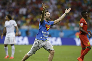 Photo - A man who ran onto the pitch gestures during the World Cup round of 16 soccer match between Belgium and the USA at the Arena Fonte Nova in Salvador, Brazil, Tuesday, July 1, 2014. (AP Photo/Matt Dunham)