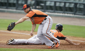 photo - Baltimore Orioles first baseman Chris Davis looks to tag out teammate Jason Pridie during  a pickoff play in a baseball spring training intra squad game Thursday, Feb. 21, 2013, in Sarasota, Fla. (AP Photo/Charlie Neibergall)