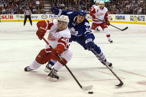 Photo - Detroit Red Wings Tomas Jurco, left, battles for the puck with Toronto Maple Leafs' Jerred Smithson during first period NHL hockey action in Toronto on Saturday, Dec 21, 2013. (AP Photo/The Canadian Press, Chris Young, File)