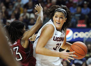 Photo - Connecticut's Stefanie Dolson (31) drives past Temple's Tyonna Williams (23) during the first half of an NCAA college basketball game in Bridgeport, Conn., Saturday, Jan. 11, 2014. (AP Photo/Fred Beckham)