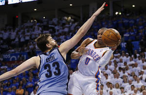 Photo - Oklahoma City Thunder guard Russell Westbrook (0) passes around Memphis Grizzlies center Marc Gasol (33) in the fourth quarter of Game 2 of an opening-round NBA basketball playoff series in Oklahoma City, Monday, April 21, 2014. Memphis won 111-105 in overtime. (AP Photo/Sue Ogrocki)