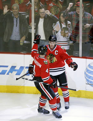Photo - Chicago Blackhawks center Jonathan Toews (19) celebrates his goal with defenseman Niklas Hjalmarsson (4) during the first period of an NHL hockey game against the Colorado Avalanche, Friday, Dec. 27, 2013, in Chicago. (AP Photo/Charles Rex Arbogast)