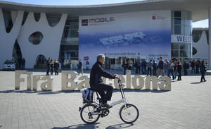 Photo - A man rides his bicycle outside  the Mobile World Congress, the world's largest mobile phone trade show in Barcelona, Spain, Sunday, Feb. 23, 2014. (AP Photo/Manu Fernandez)
