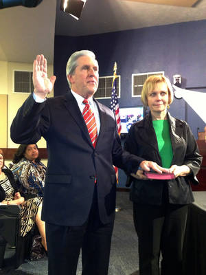 Photo - Edmond Ward 4 Councilman Nick Massey takes the oath of office. His wife, Dr. Karen Mahlmeister, holds the Bible. PHOTO BY DIANA BALDWIN, THE OKLAHOMAN. <strong>Diana Baldwin - THE OKLAHOMAN</strong>