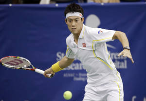 photo - Kei Nishikori, of Japan, returns a shot to Marinko Matosevic, of Australia, in a semifinal round tennis match at the U.S. National Indoor Championships on Saturday, Feb. 23, 2013, in Memphis, Tenn. (AP Photo/Mark Humphrey)
