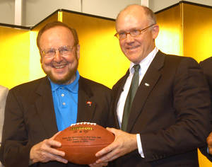 Photo - FILE - In this July 31, 2003 file photo, Tampa Bay Buccaneers owner Malcolm Glazer, left, and his New York Jets counterpart Robert Woody Johnson smile as they hold a football together during a press conference at Tokyo Dome hotel in Tokyo. Glazer, the self-made billionaire who owned the NFL's Tampa Bay Buccaneers and English soccer's Manchester United, has died.  He was 85. The Bucs said Glazer died Wednesday, May 28, 2014. (AP Photo/Katsumi Kasahara, File)