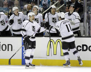 Photo - Los Angeles Kings' Anze Kopitar (11), of Slovenia, celebrates with teammates on the bench after scoring against the San Jose Sharks during the second period of an NHL hockey game on Monday, Jan. 27, 2014, in San Jose, Calif. (AP Photo/Marcio Jose Sanchez)