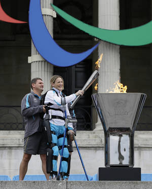 Photo -   Claire Lomas lights the Paralympic flame cauldron in Trafalgar Square in London, Friday, Aug. 24, 2012. Claire had a horse riding accident in 2007 leaving her paralysed from the chest down. The London Paralympics begin on Wednesday Aug. 29. (AP Photo/Kirsty Wigglesworth)