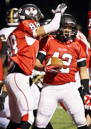 Photo - Caleb Newman (88) and Caleb Davis (42) celebrate a touchdown by Davis in the second quarter during a high school football game between Yukon and Midwest City in Yukon, Okla., Thursday, Oct. 24, 2013. Photo by Nate Billings, The Oklahoman