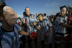 "Photo - FILE - In this Wednesday, July 9, 2014 file photo, soccer fans of the Argentina national soccer team wear masks with faces of Pope Francis and Argentine soccer player Lionel Messi during a live telecast of the soccer World Cup semifinal match between Argentina and Netherlands, inside the FIFA Fan Fest area on Copacabana beach, in Rio de Janeiro, Brazil. The Vatican says it is unlikely that Pope Francis and his predecessor, Pope Emeritus Benedict XVI, would get together to watch their home teams in the World Cup final on Sunday. Vatican spokesman, the Rev. Federico Lombardi, said Thursday, July 10, 2014 that the hour of the final is late for Francis' routine, and acknowledged with a chuckle that Benedict wasn't known as an avid sports fan. Still, he didn't rule anything out, saying, ""we'll see in the coming days."" Pope Francis has already given his word that there would be no papal intervention in Argentina's fortunes, promising he wouldn't pray for any team. German-born Benedict's interests are known to lean more toward intellectual than athletic pursuits. (AP Photo/Silvia Izquierdo, File)"