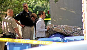 Photo - Morticians and Logan City police officers remove one of two gunshot victims from apartment complex Monday, July 14, 2014, in Logan, Utah.  Police say three people have been found shot dead in two different locations in Logan. Police say they responded to reports of gunfire at an apartment just after midnight.   Police say they found a man and a woman dead inside one of the units. Officers say they received another 911 call around 1 a.m. reporting a gunshot at a west Logan home and found a man dead of what appears to be a self-inflicted gunshot wound. Police suspect the two incidents are connected. (AP Photo/The Herald Journal, Jeff Hunter)