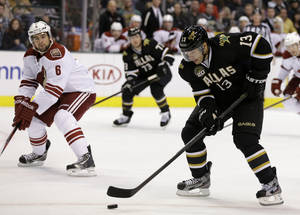 Photo - Dallas Stars' Ray Whitney (13) prepares to take a shot on-goal under pressure fro Phoenix Coyotes' David Schlemko (6) in the first period of an NHL hockey game on Friday, Feb. 1, 2013, in Dallas. (AP Photo/Tony Gutierrez)