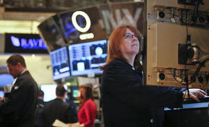Photo - FILE - In this Feb. 20, 2013, file photo, Maureen Smaldone, a trader for Brendan E. Cryan and Company, monitors trading activity from her workstation at the New York Stock Exchange. U.S. stocks are continuing a two-day slide on weak economic data on Thursday, Feb. 21, 2013, and concern that the Federal Reserve may cut back its bond-buying program. (AP Photo/Bebeto Matthews)