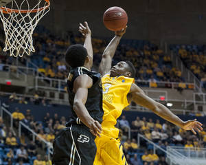 Photo - West Virginia's Juwan Staten, right, looks to dunk over a Purdue defender during the second half of an NCAA college basketball game on Sunday, Dec. 22, 2013, in Morgantown, W.Va. Purdue won 73-70. (AP Photo/Andrew Ferguson)
