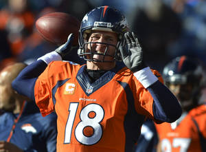 Photo - Denver Broncos quarterback Peyton Manning warms up before playing against the San Diego Chargers in an NFL AFC division playoff football game, Sunday, Jan. 12, 2014, in Denver. (AP Photo/Jack Dempsey)