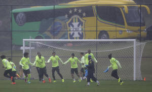 Photo - Member of the Brazilian national soccer team exercise in the rain during a team training session in Teresopolis, Brazil, Thursday, June 19, 2014. Brazil plays in group A of the 2014 soccer World Cup. (AP Photo/Andre Penner)