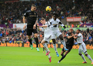 Photo - Manchester City's Aleksandar Kolarov, left, battles for the ball with Swansea City's Ben Davies and Wilfried Bony, right, during their English Premier League soccer match at the Liberty Stadium, Swansea, Wales, Wednesday Jan. 1, 2014. (AP Photo/PA, Nick Potts) UNITED KINGDOM OUT  NO SALES  NO ARCHIVE