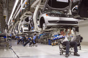 Photo - FILE - In this July 12, 2013, photo, employees at the Volkswagen plant in Chattanooga, Tenn., work on the assembly of a Passat sedan. Volkswagen on Monday, July 14, 2014 said it will build a new seven-passenger SUV at the Chattanooga factory, adding about 2,000 jobs. (AP Photo/Erik Schelzig, File)