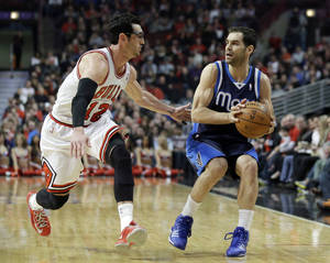 Photo - Dallas Mavericks guard Jose Calderon, right, looks to a pass as Chicago Bulls guard Kirk Hinrich defends during the first half of an NBA basketball game in Chicago on Saturday, Dec. 28, 2013. (AP Photo/Nam Y. Huh)